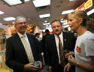 Donald Schroeder, president and CEO of Tim Hortons Inc. and David Clanachan, Tim Hortons COO talk with an employee during the opening of a new Tim Hortons coffee and bake shop in New York's Penn Station