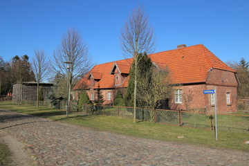Former foal stable on palace grounds in Griebenow, Mecklenburg-Vorpommern, Germany. The street name sign says Schlossweg - Palace way