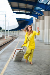 Young woman with suitcase walking for her train railway station