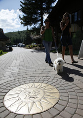 People walk their dog past a sun logo on a sidewalk at the Sun Valley Resort in Sun Valley