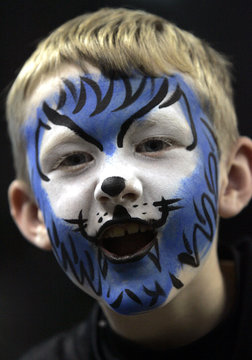 With his face painted like a blue lion, Kerbyson roars as he watches Detroit Lions warm up before start of their NFL football game against the Washington Redskins in Detroit