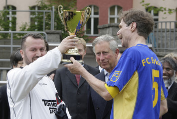 Britain's Prince Charles hands over trophy to team captains after inter-religion soccer match in Berlin
