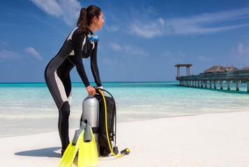 Weibliche Taucherin mit Ausrüstung am tropischen Strand der Malediven