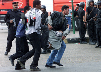 CAIRO UNIVERSITY STUDENTS CARRY COLLEAGUE OVERCOME BY TEAR GAS DURINGDEMONSTRATION.