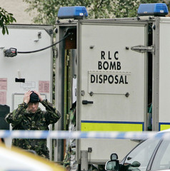 A member of an Army bomb disposal unit attends the scene as a house is searched in connection with ...