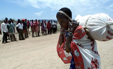 An unidentified Maasai woman (R) carries home food rations from relief distributiopns at the Elang'a..