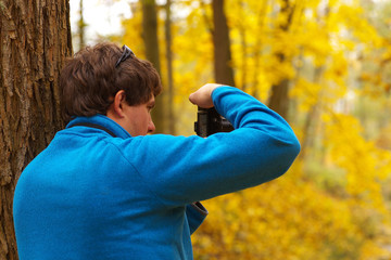 Man leaning against a tree and taking photo of an autumnal forest