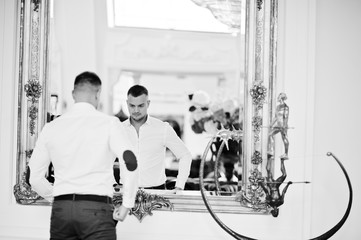Fashionable man against mirror at white dress indoor royal palace.