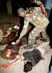 ARMY SOLDIERS LOOK AT BODY OF PEOPLE KILLED BY A FORMER INDIAN SOLDIER IN A GUN BATTLE IN GUWAHATI.