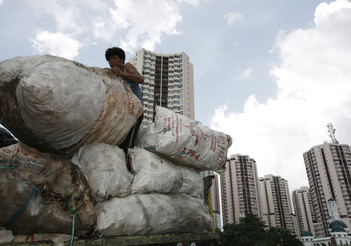 A worker loads plastic for recycling onto a truck near luxury apartments in Jakarta