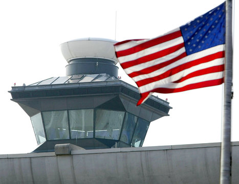 An American flag flies with the air traffic control tower in the background at Dulles International ..