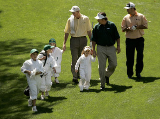 Golfers Jim Furyk, Phil Mickelson and Chris DiMarco walk with their children as they play in annual par-three tournament in Augusta