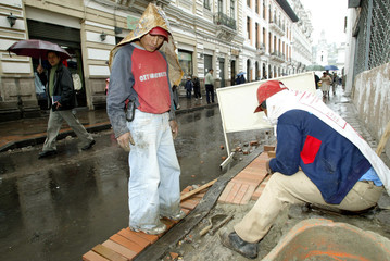 Municipal workers fix a sidewalk outside Carondelt Palace after it was damaged by demonstrators in ...