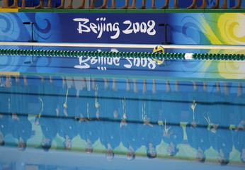 Reflection of members of the Australian team is seen as they stand side by side before the start of their women's preliminary round Group B water polo match against Greece at the Beijing 2008 Olympic Games