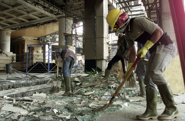 A GROUP OF WORKERS CLEAR PIECES OF GLASS FROM NEAR THE BOMB SITE INJAKARTA.