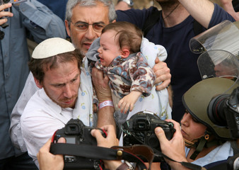 An Israeli paramedic and policewoman hold a settler's baby during an eviction of a house in Hebron