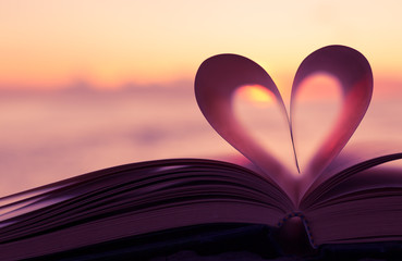 Heart shaped paper book against sunset.