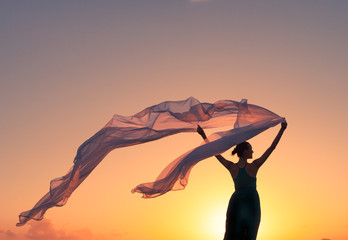 Feeling free! Female holding a silk cloth blowing in the wind.
