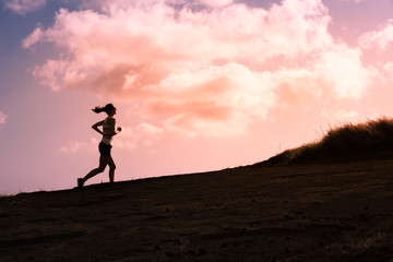 Silhouette of female running up a hill.