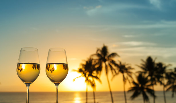 Romantic beach holiday retreat concept. Pair of wine glasses against a beautiful beach setting.