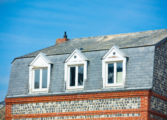 photo of beautiful roof of one on the buildings on the wonderful sunny sky background, France, Normandy