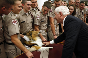 Gates greets a mascot and cadets after attending the Points of Light forum in Texas
