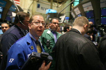 Traders gather at the kiosk where GM is traded on the floor of the New York Stock Exchange