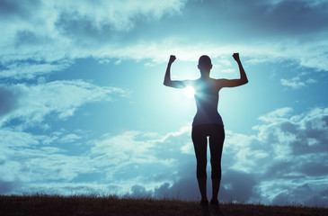 Silhouette of strong and confident woman flexing.