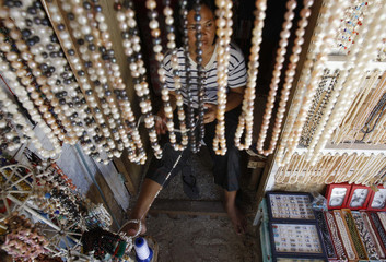 Woman makes a necklace for sale to tourists at Puka beach in Boracay
