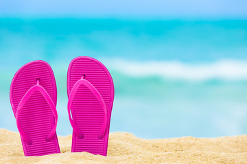 Pair of pink slippers on a beautiful white sand beach.
