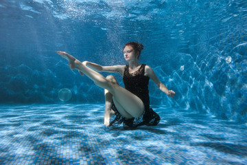 Dancing woman under the water in the pool. Surrealistic photography.