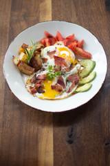 Eggs over medium with a side of avocado, bacon, potato, and tomato