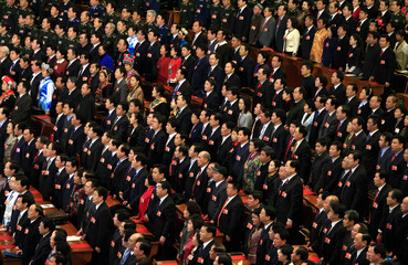Delegates stand as they sing the Chinese national anthem during the closing ceremony of the NPC in Beijing