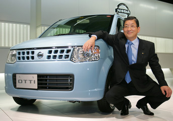 "Toshiyuki Shiga, Chief Operating Officer of Nissan Motor Co., poses next to the new ""Otti"" mini-vehicle at the company headquarters in Tokyo"