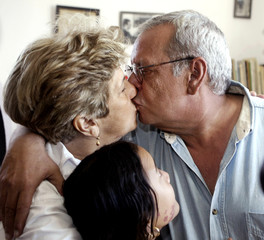 Cuban dissident poet and journalist Raul Rivero (R) kisses his wife Blanca as their daughter Yenia l..