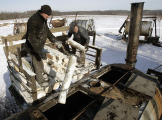 Workers throw logs of wood into a furnace to produce charcoal in village of Volkovishche