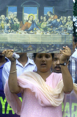 AN INDIAN CHRISTIAN WOMAN HOLDS A PICTURE DEPICTING THE LAST SUPPER DURING A PROTEST IN CALCUTTA.