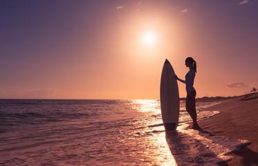 Female surfer girl on the beach.
