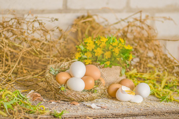 Easter rustic background with chicken eggs in straw nest on old board