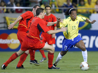 BRAZIL'S RONALDINHO IS CHALLENGED BY BELGIUM'S SIMONS DURING WORLD CUPMATCH IN KOBE.
