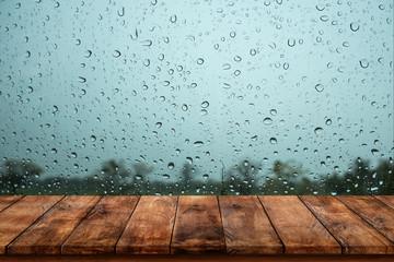 Wood table with rain water drop on window.