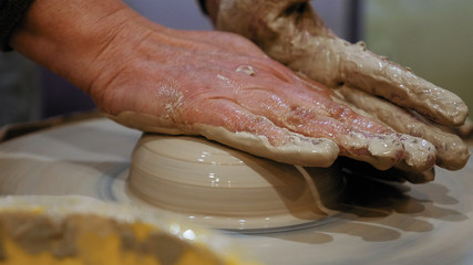 Potter is making clay pot bowl or vase ceramics porcelain on the potter's wheel. Creating pottery art and handicraft modelling creation.