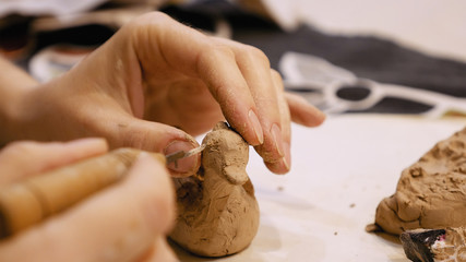 Female sculptor is modeling clay figurine or creating pottery ceramics statuette. Art and handicraft modelling creation.