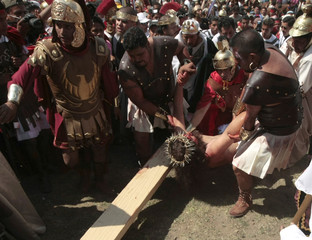Diego Villagran, 18, is carried during a re-enactment of the crucifixion of Jesus Christ in Iztapalapa district