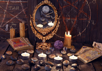 Magic ritual with ancient runes, mirror, tarrot cards and candles