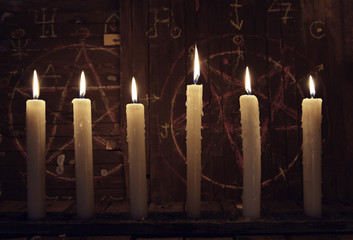 Mystic close up wih burning candles against wooden background with magic symbols