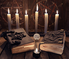 Esoteric still life with two black magic books and burning candles