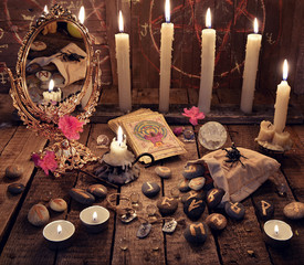 Mystic ritual with burning candles, magic mirror, flowers and the tarot cards. Divination rite