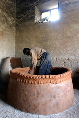AFGHAN MAN MAKES A LOCAL TANDOOR OVEN IN KABUL.