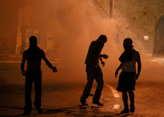 Israeli-Arab stone throwers walk on the street after clashes erupted in Acre